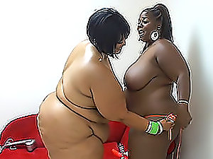 Two adult black fatties have a girl-on-girl fuck on the sofa