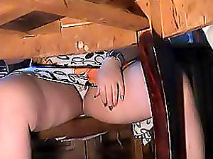 A dirty mind dude tapes the woman sitting on the table underneath