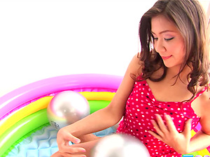 Asian in an inflatable pool pumping a buttplug into her cootchie