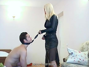 Blonde mistress in high high-heeled shoes steps over the chest of her victim