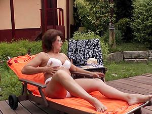 Fat mature bimbo likes fingerblasting her cunt in the sun