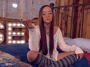 Long-haired sweet thing Jessie Lynne sits on her bed wearing leggings
