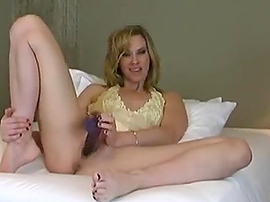 A lustful blonde milf masturbates with the help of a black rubber toy in front of a camera