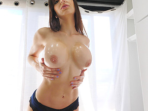 Busty brunette oils her tits and tosses them around for the camera