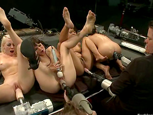 Four pretty women have fun with a few fucking machines in a basement