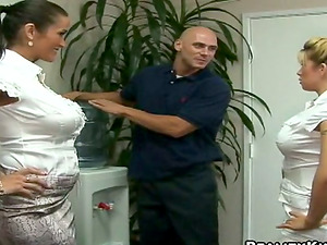 Two well-endowed gals share some dude's schlong in an office