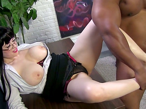 A buxom assistant gives a footjob to Black fellow in an office