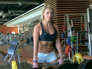 A pretty blonde in sportswear shows her breasts in a gym