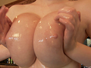 Felicia plays with her big faux tits in the kitchen