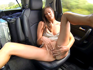 Horny brown-haired masturbates with a faux-cock in the backseat of a car