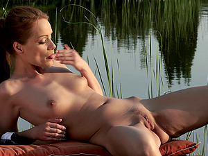 Chilling by a tranquil lake and stimulating her sore snatch