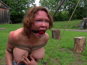 Thick stunner is tied up and tantalized in the green backyard