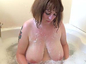 British babe Mia Wallace in the bath soaping up her giant boobs and round ass