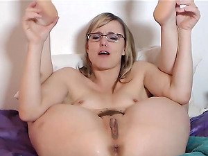 Hot mature woman with short hair and glasses is masturbating her hairy pussy