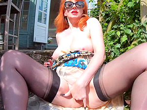 Busty Red fingers herself in the garden