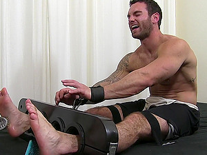 Laughing man tied up to a BDSM device and tickled until orgasm