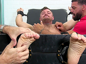 Laughing dude enjoys during feet tickling by his two friends