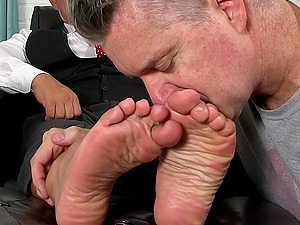 Business man makes his dirty assistant lick his shoes and feet