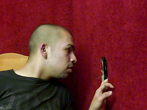 Gay guy strokes his penis while sucking a black dick thru a gloryhole