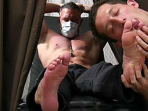 Muscular guy with a mask enjoys while his pervert friend licks his feet