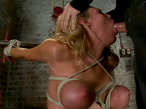 He catapults his penis in her mouth, having her tied up on the yoke bar